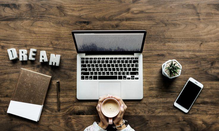 Mann hält Kaffeetasse in seinen Händen; davor Laptop, Smartphone und Büro-Utensilien